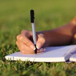 http://www.dreamstime.com/royalty-free-stock-photo-close-up-woman-hand-writing-notebook-outdoor-lying-grass-park-image43632445